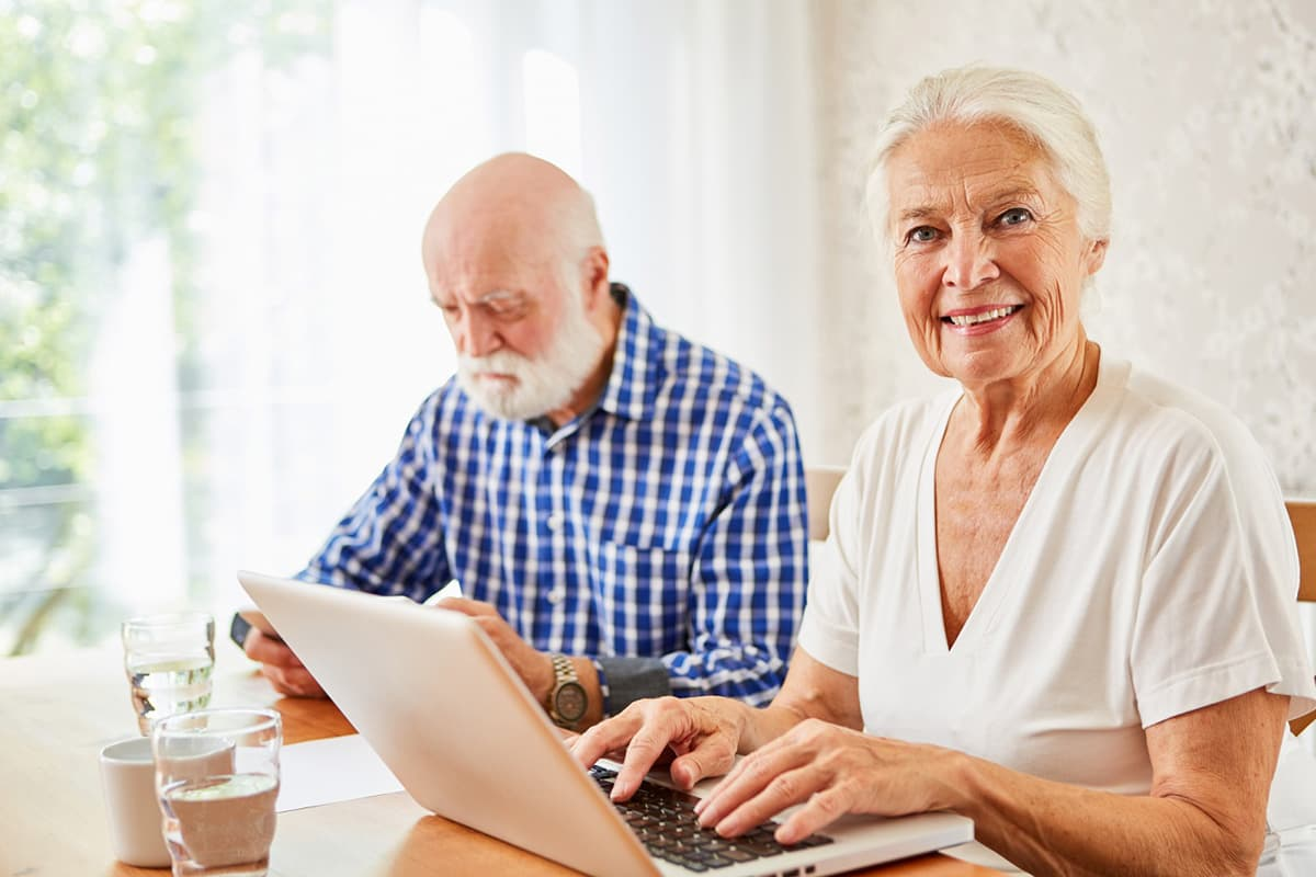 A happy elderly couple, enjoying independent senior living, learning a foreign language together in their North Shore retirement apartment.