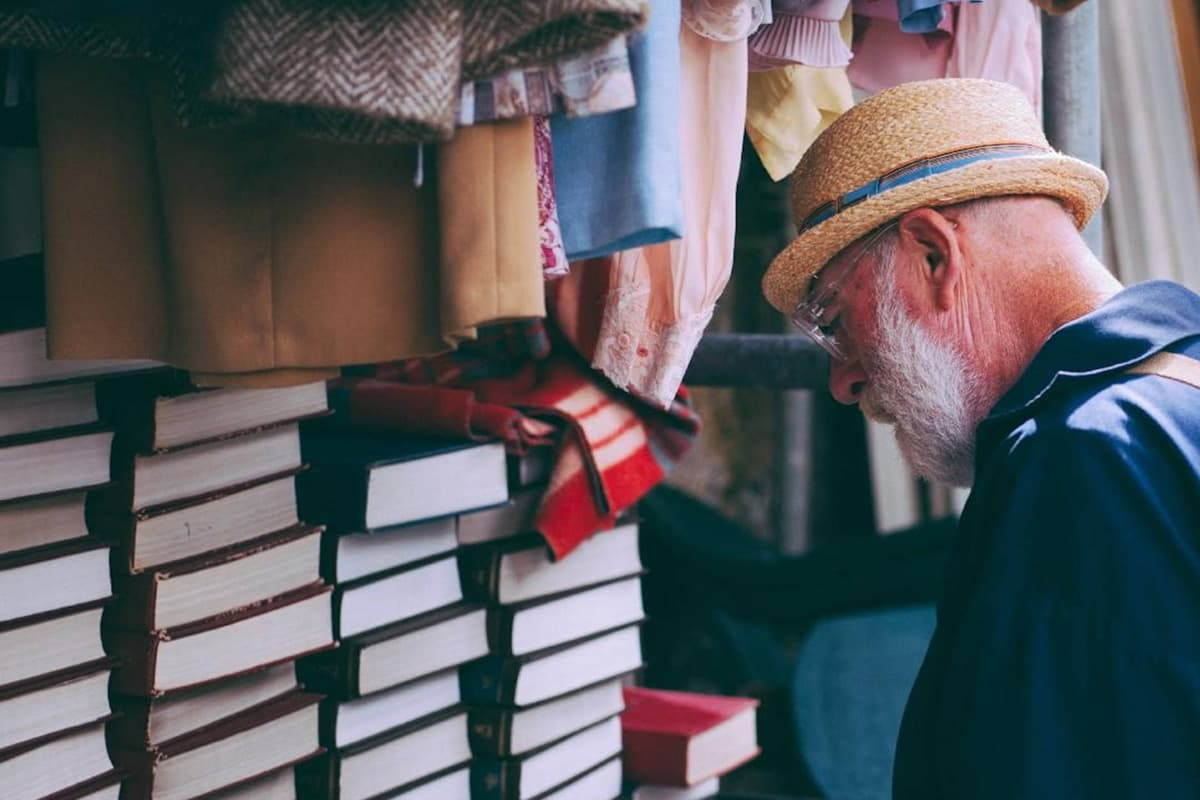 Elderly man looking at pile of books