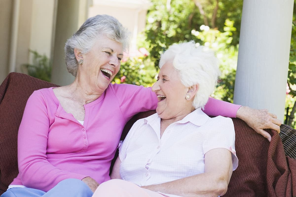 Two senior women friends sitting on a couch and laughing, enjoying the advantages of independent senior living in retirement.
