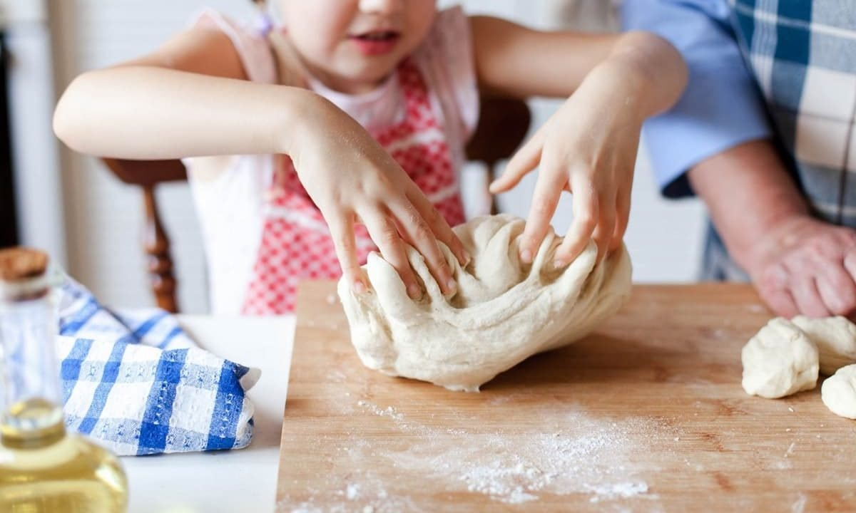 Kid playing with dough, making pizza in the kitchen with grandma
