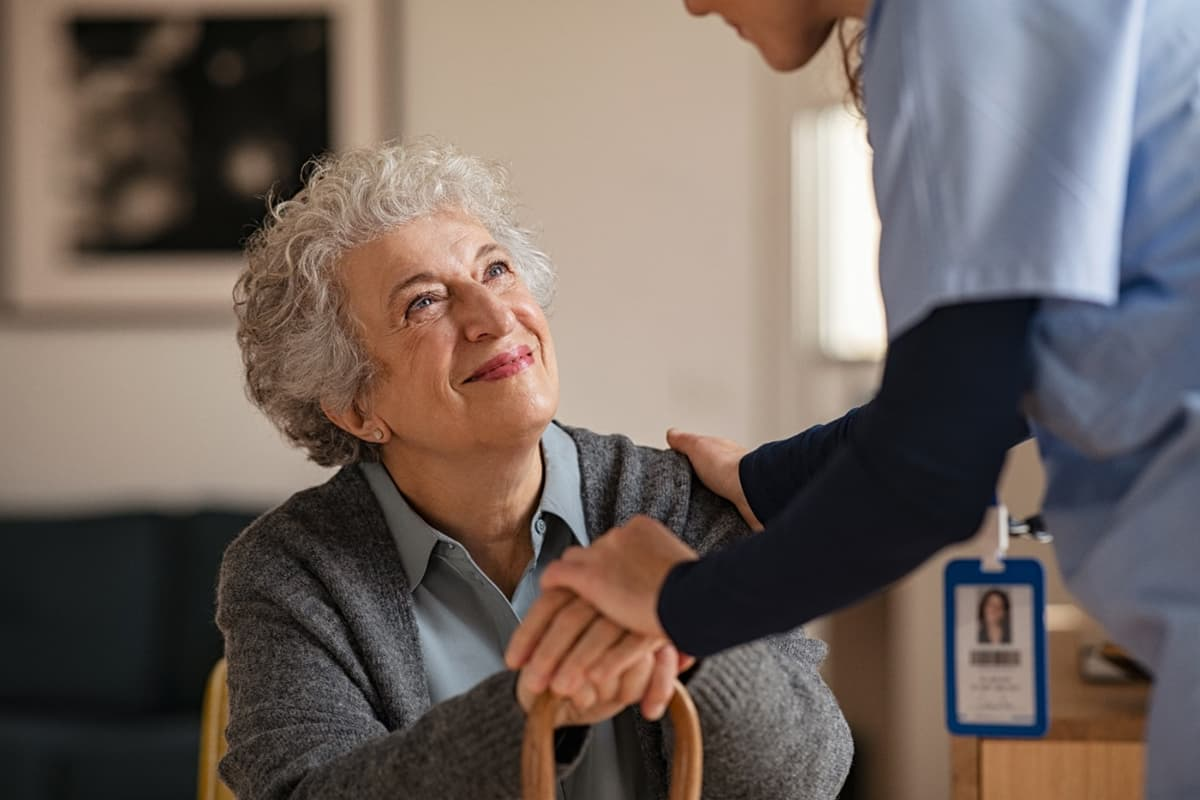 Happy senior woman talking to a caregiver visiting her in her retirement home.